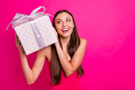 Close-up portrait of nice attractive gorgeous cheerful curious long-haired girl holding in hands festal box guessing whats inside isolated on bright vivid shine vibrant pink fuchsia color background