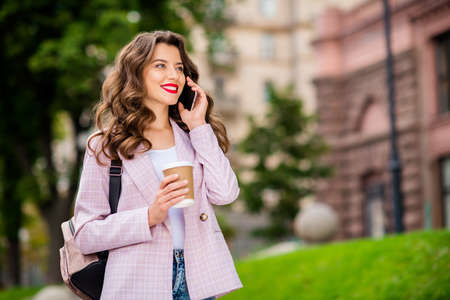 Portrait of her she nice-looking attractive lovely charming cheerful cheery wavy-haired lady foreign tourist making call home telling stories in park fresh air downtown center outdoors