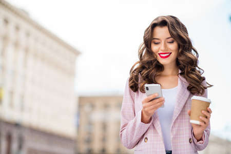 Close-up portrait of nice-looking attractive charming glamorous lovely cheerful cheery wavy-haired businesslady using new modern technology 5g app web service in town center outdoors