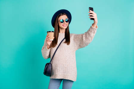 Portrait of stylish trendy positive lady make self portrait on her cell phone wear cap hat white knitted jumper isolated over teal turquoise color background