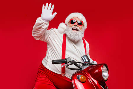 Portrait of his he nice bearded cheerful funky Santa hipster riding motor bike waving congratulating you North Pole congrats isolated on bright vivid shine vibrant red color background