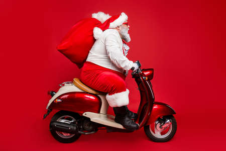 Profile side view portrait of nice bearded serious Santa Saint Nicholas father riding moped delivering big sack purchase shopping concept isolated on bright vivid shine vibrant red color background