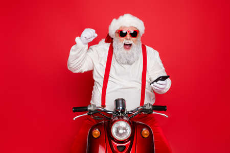 Portrait of nice attractive bearded cheerful cheery glad funny funky Santa wearing cap hat sitting on motor bike using cell good news isolated over bright vivid shine vibrant red color background