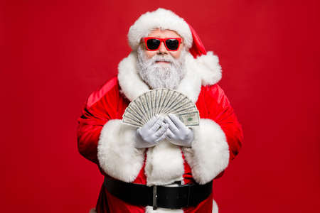 Portrait of cool strylish elderly santa claus hipster millionaire have cash want buy presents spend on winetr season sales discount wear cap hat eyewear eyeglasses isolated over red background Banque d'images - 131818868