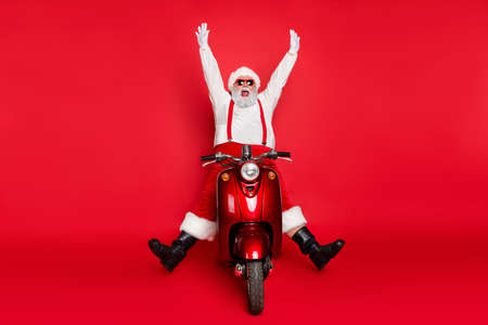 Portrait of his he nice attractive carefree crazy bearded cheerful cheery funny funky Santa riding bike delivering orders having fun isolated over bright vivid shine vibrant red color background Standard-Bild