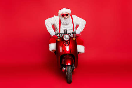 Portrait of his he nice attractive bearded cheerful brutal virile Santa Claus riding bike delivering orders winter shopping concept isolated over bright vivid shine vibrant red color background Imagens - 131818271
