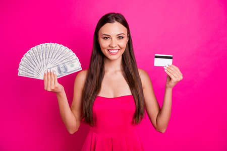 Portrait of her she nice attractive cheerful confident long-haired girl holding in hand big sum budget plastic atm card isolated on bright vivid shine vibrant pink fuchsia color background