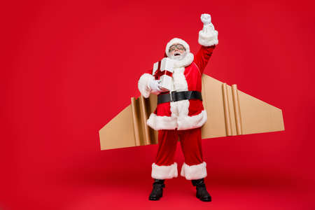 Hurry to give presents. Full size photo of fun super elderly santa launch to fly up in magic cardboard travel wings have grey hair wear pants cap hat gloves isolated over red background