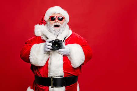 Portrait of excited enthusiastic santa claus in eyewear eyeglasses have voyage take photo wear stylish costume cap hat belt isolated over red background Imagens