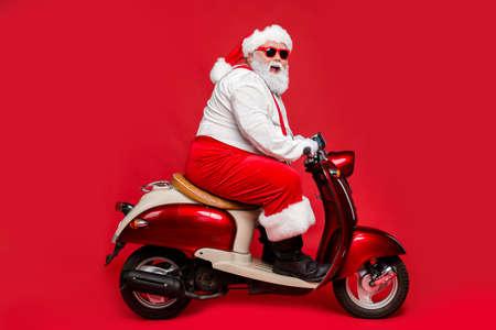 Profilseitenansicht Porträt eines netten bärtigen fröhlichen fröhlichen lustigen Weihnachtsmannes, der Motorrad fährt und Spaß beim Einkaufen in der Wintersaison hat, einzeln auf hell leuchtendem, leuchtend rotem Hintergrund