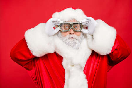 Close up photo of focused funky cool santa claus fix his goggles before rocket flight wear white gloves cap isolated over red color background