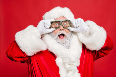 Close up photo of impressed funny santa claus touch his travel turbo glasses see winter season sales discount wear white gloves cap hat isolated over red color background