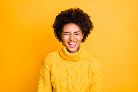 Photo of pretty dark skin lady laughing out loud with closed eyes wear warm knitted jumper isolated yellow color background