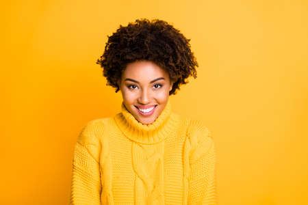 Photo of amazing dark skin lady with sweet beaming smile wear warm knitted pullover isolated yellow background 版權商用圖片