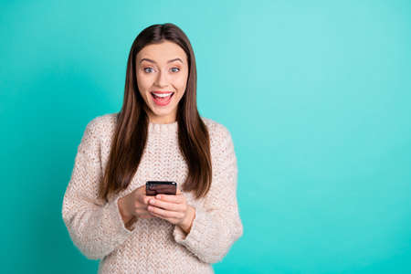 Portrait of inpressed funky teen blogger use her cell phone got news from social account wear knitted woolen jumper isolated over teal turquoise color background Banco de Imagens