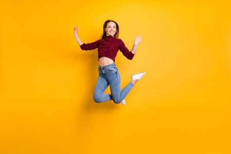 Foto in voller Größe von hübscher Jugend, die mit einem zahnigen Lächeln aussieht und einen kastanienbraunen Pullover trägt, der auf gelbem Hintergrund isoliert ist