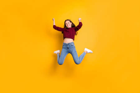 Full length photo of delighted woman with her closed eyes and long haircut raising fists wearing burgundy sweater isolated over yellow background 版權商用圖片 - 132014294