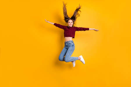 Full length photo of charming lady raising her arms wearing burgundy pullover isolated over yellow background Banco de Imagens