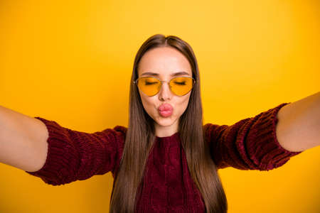 Close up photo of lovely girl in eyewear eyeglasses sending air kisses closing her eyes wearing maroon sweater isolated over yellow background