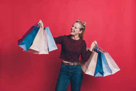 Omg I am crazy shopper concept. Photo of excited positive cheerful delightful nice glad charming hipster girl in jeans holding big bags with clothes isolated background Stok Fotoğraf