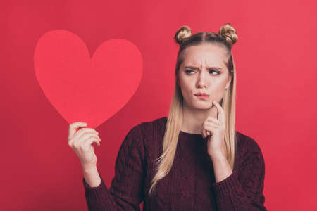 Yes or no. Ready or not. I am too young for dating concept. Close up photo of confused hipster do not know what to react on comment like or dislike holding large heart isolated background Stock Photo