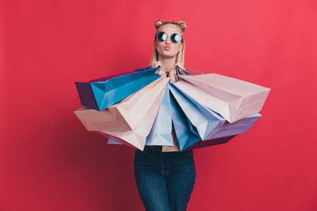 great hot big seasonal sales concept. Photo of nice positive with blow pouted plump lips hipster wearing jeans denim clothes holding different many bags in hands isolated pastel background Banco de Imagens