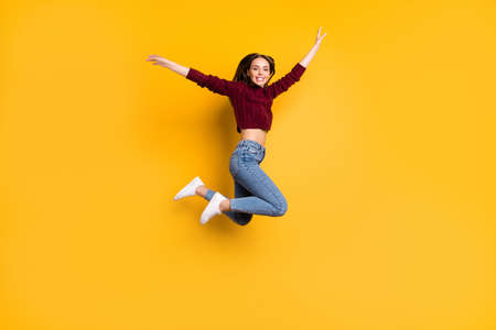 Full length photo of lovely girl smiling raising her arms smiling wearing marsala pullover isolated over yellow background Stockfoto