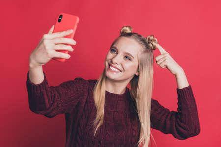 Foto einer Influencer-Dame, die ein Telefon in der Hand hält und Selfies macht, die den Anhängern eine neue Frisur zeigen, tragen einen gestrickten Pullover isolierten pastellroten Farbhintergrund