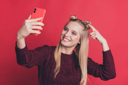 Photo of influencer lady holding telephone in hand making selfies showing new hairstyle to followers wear knitted jumper isolated pastel red color background