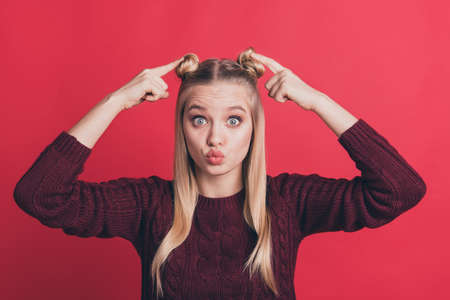 Photo of pretty lady indicating fingers on own head hair buns advising visit cool stylist salon sending air kiss wear knitted pullover isolated pastel red color background
