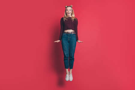 Full length photo of funny attractive lady jumping high rejoicing in flight wear knitted burgundy pullover and jeans isolated pastel red color background
