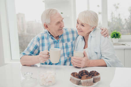 Close up photo of lovely couple hold hand beverage mug enjoy weekend sit table indoors