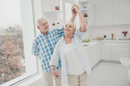 Portrait of charming sweet grandparents memory ballroom dancing kitchen enjoy kitchen room indoors Stock Photo