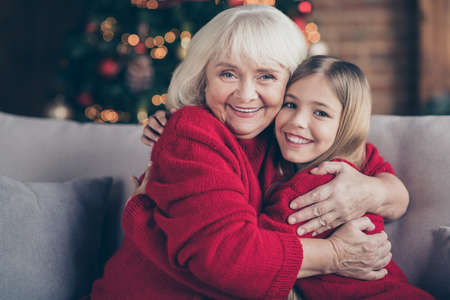 Close-up portrait of nice attractive lovely sweet glad tender affectionate cheerful cheery granny grandchild sitting on cosy divan hugging tradition at decorated industrial loft style interior house Reklamní fotografie