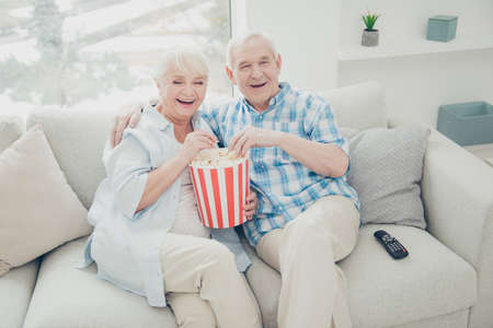 Above high angle view of two nice attractive cheerful cheery positive spouses having fun spending free time watching serial funny cinema in light white interior living-room indoors