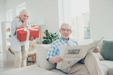 Portrait of her she his he two nice attractive lovely cheerful cheery people granny carrying big large romantic gift for grandpa in light white interior living-room house
