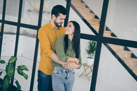 Photo of handsome guy and his pretty wife lady looking tender eyes moved to new flat hugging piggyback in modern trendy interior flat indoors wear casual clothes