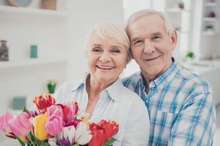 Close-up portrait of her she his he two nice attractive lovely cheerful cheery adorable people granny holding in hands big fresh natural blossom congrats spring in light white interior living-room Stock Photo