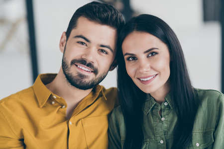 Close up photo of handsome guy and his wife lady moving to first flat as married people beginning new life in stylish interior flat indoors wear casual clothes