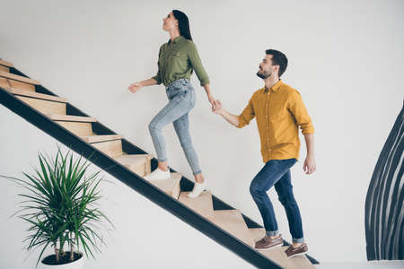 Full body profile photo of handsome guy and his pretty lady leading macho to bedroom going up stairs in modern interior hotel room indoors wear casual clothes Stok Fotoğraf