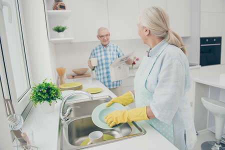 Photo of charming couple drying wet dishes have dialogue share information newspaper stand indoors