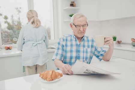 Close up photo of focused man sit table croissant hold hand beverage mug look news indoors
