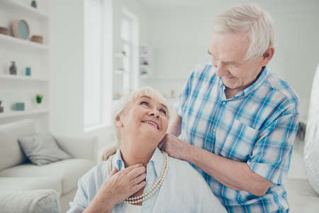 Photo of two adorable aged people pair spending time together holiday surprise pearls necklace comfortable flat indoors