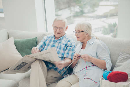 Photo of two pretty aged people pair spending time together reader fresh article sitting sofa comfortable bright flat indoors Stock Photo