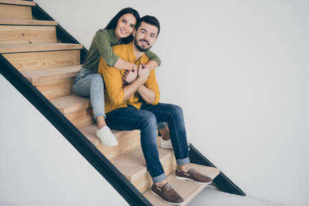 Full body profile photo of handsome guy and his pretty lady sitting comfy on stairs in modern room indoors moving to new flat together wear casual clothes Stock Photo