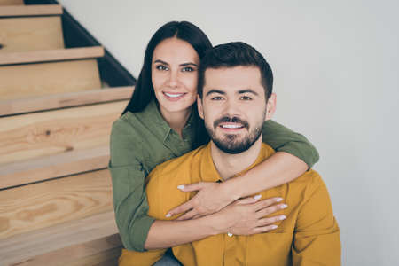 Closeup photo of handsome guy and his pretty lady sitting on stairs in modern interior room indoors moving to new flat house together wear casual clothes Stock Photo