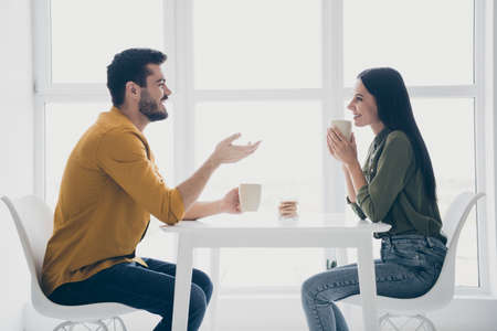 Profile photo of handsome guy and his pretty lady looking tender eyes drinking hot beverage sitting chairs opposite in modern interior light cafe indoors wear casual clothes
