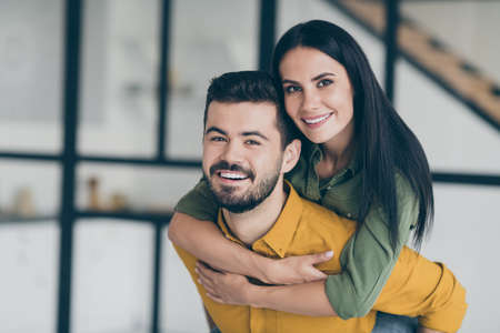 Closeup photo of just married husband guy and his wife lady holding piggyback carry bride to new bought flat showing unexpected wedding surprise wear casual clothes