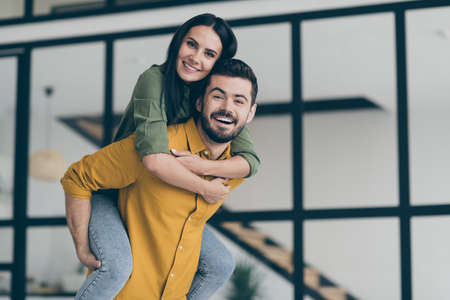 Just married. Photo of handsome husband guy and his wife lady excited to start honeymoon in modern country house flat holding piggyback wear casual clothes