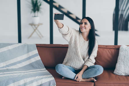 Portrait of positive cheerful girl hold cellphone take selfie photo sit on divan in house modern apartment feel content wear knitted sweater denim jeans
